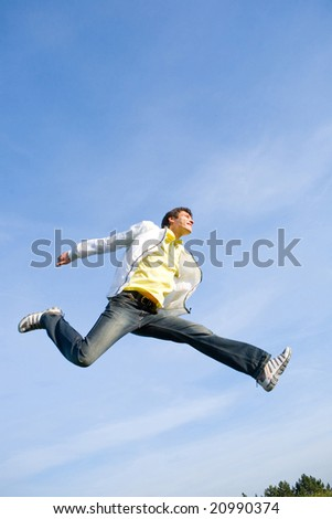 Happy young man - jumping  end flight in blue sky. - stock photo