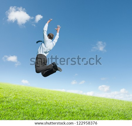 happy young man jumping on meadow against clear sky background - stock photo