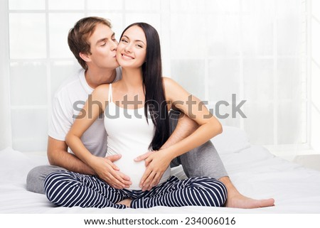 Happy young man kissing her pregnant smiling wife - stock photo