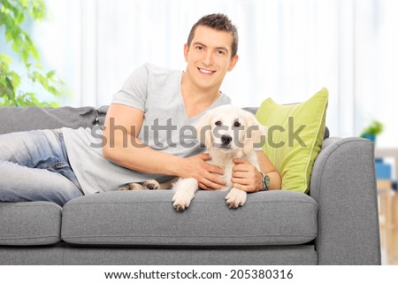 Happy young man lying on a couch with a Labrador puppy at home - stock photo