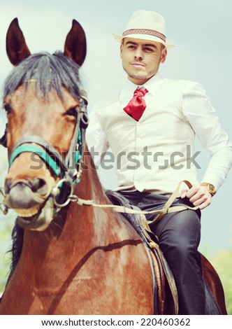 Happy young man on countryside with horse for riding - stock photo