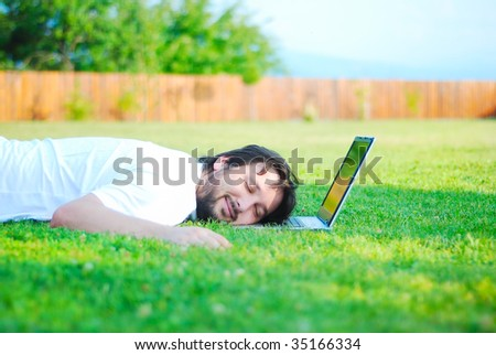 Happy young man on green meadow with laptop - stock photo
