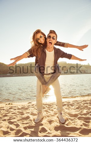 Happy young man piggybacking his girlfriend at the seaside - stock photo