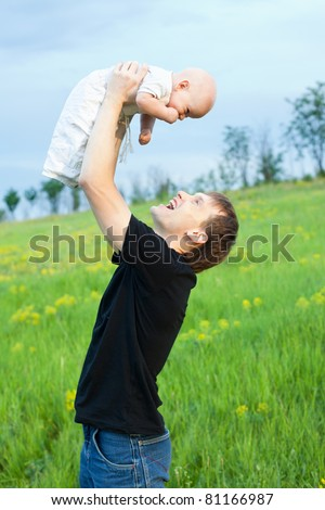 happy young man playing his baby boy on nature on slope - stock photo