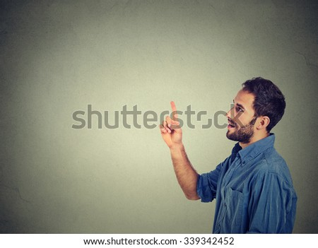 Happy young man pointing looking at copy space. Handsome young businessman isolated on gray wall background. - stock photo