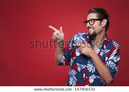 Happy young man pointing sideways  - stock photo