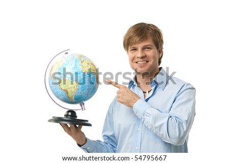 Happy young man pointing to globe in his hand, smiling. Cutout.
