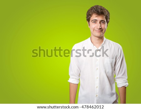Happy young man posing on green background