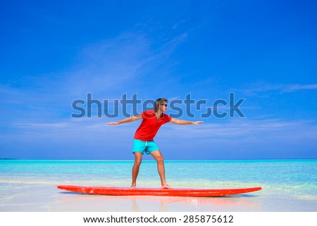 Happy young man practicing surfing position on surfboard  - stock photo