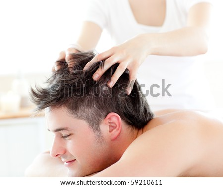Happy young man receiving a head massage in a spa center - stock photo