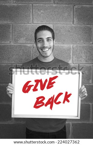 happy young man showing and displaying board with text: Give back Campaign - stock photo