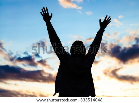 Happy Young Man Silhouette with Hands Up on the Evening Sky Background
