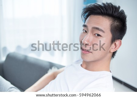 Happy young man sits on sofa and looks at camera
