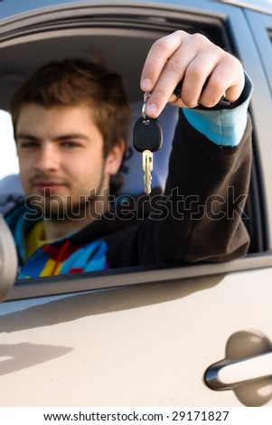 Happy young man sitting in a new car holding out keys