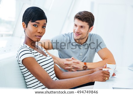 Happy young man sitting in cafe and drinking coffee with young african woman