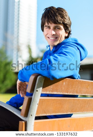 Happy Young Man Sitting On Bench In Park - stock photo