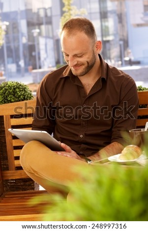 Happy young man sitting on bench, using tablet in outdoor cafe. - stock photo
