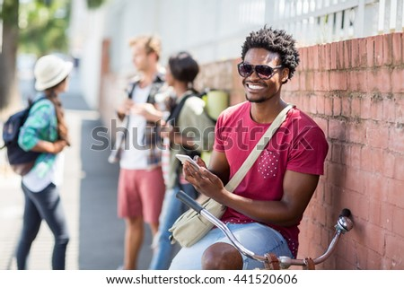 Happy young man sitting on bicycle using mobile phone with friends interacting background - stock photo