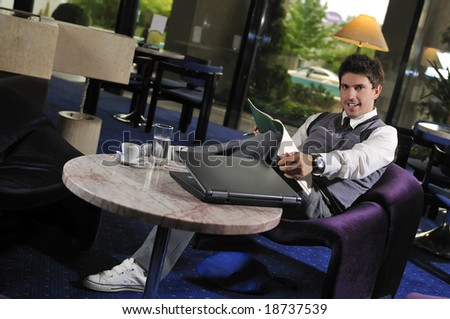 Happy young man sitting relaxed working on computer - stock photo