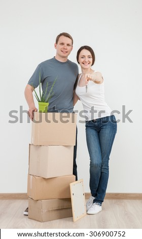 Happy young man standing near cardboard boxes,  his smiling wife holding bunch of keys, neutral background - stock photo