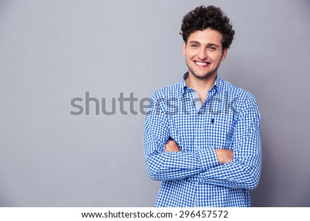 Happy young man standing with arms folded over gray background - stock photo