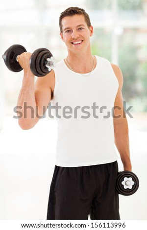 happy young man training with dumbbells at the gym