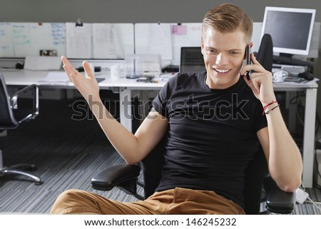 Happy young man using cell phone at office
