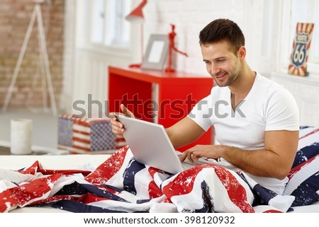 Happy young man using laptop computer in bed, smiling. - stock photo