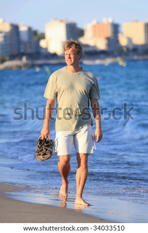 Happy young man walks close to the sea - stock photo
