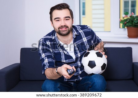 happy young man watching football on tv - stock photo