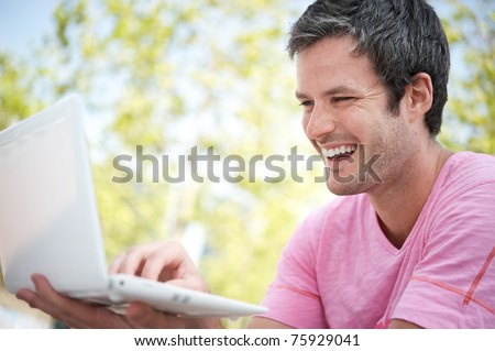 Happy young man with a laptop outdoors - stock photo