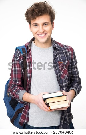 Happy young man with backpack and books over gray background - stock photo