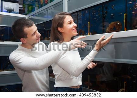 happy young man with girlfriend choosing aquarium fish in aquarium - stock photo