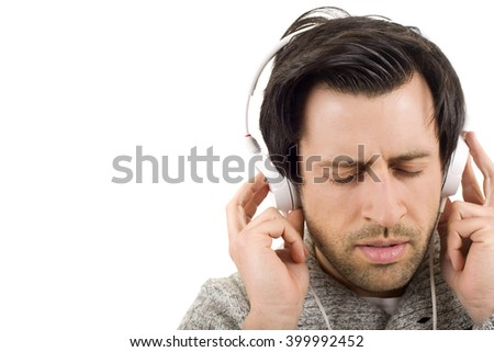 Happy young man with headphones, listening to music with eyes closed, isolated - stock photo