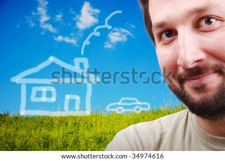 Happy young man with imagination of house and car on beautiful meadow