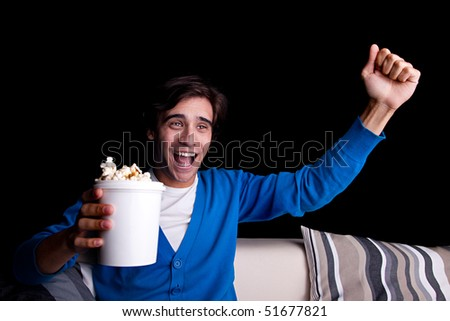 happy young man, with popcorn watching, on black background. Studio shot - stock photo