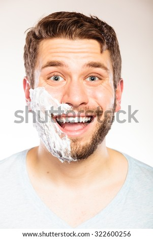 Happy young man with shaving cream foam on half of face beard. Handsome guy preparing to shave. Skin care and hygiene. - stock photo