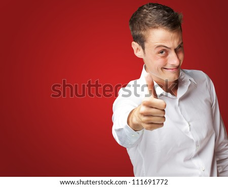 Happy Young Man With Thumbs Up On Red Background - stock photo