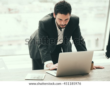 Happy young man working on laptop while sitting at his working place in office - stock photo