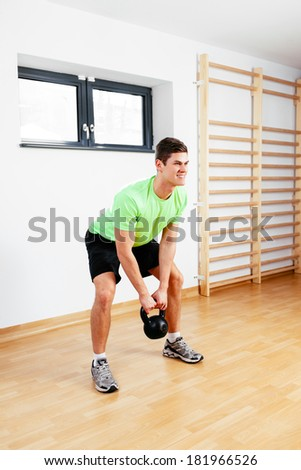 Happy young man working out with kettlebell