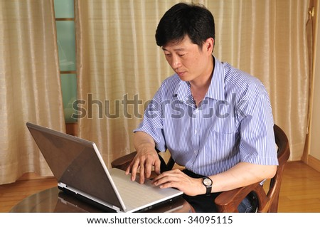 Happy young man working with laptop in the office