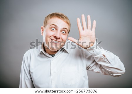 Happy young manager or student waving his hand - stock photo