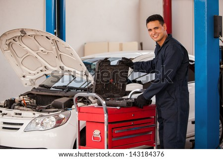 Happy young mechanic looking for some tools for work at an auto shop - stock photo