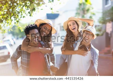 Happy young men giving piggyback to women - stock photo