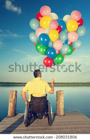 Happy young men in wheelchair holding colorful balloons on wooden boardwalk at lake - stock photo