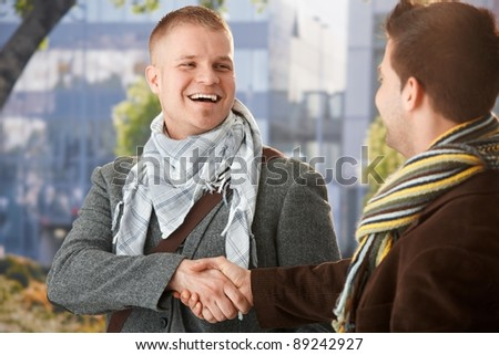 Happy young men shaking hand in greeting, laughing, standing outdoors in trendy clothes.? - stock photo