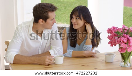 Happy young mixed couple sitting at table