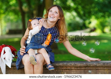 Happy young mother and adorable toddler girl blowing soap bubbles and having fun together, outdoors. - stock photo