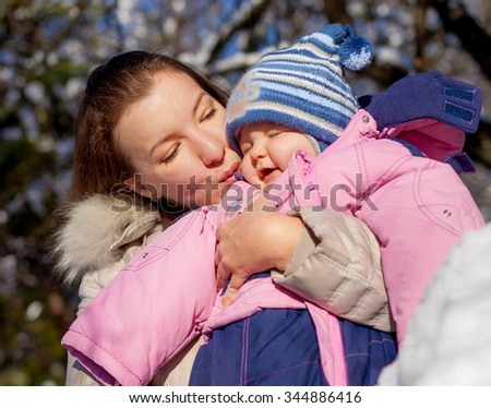 Happy young mother and baby  in winter park