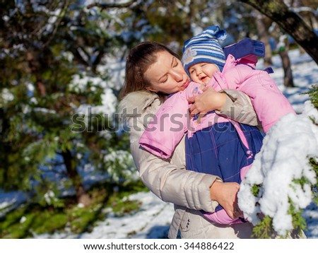 Happy young mother and baby  in winter park - stock photo